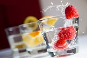 Glass of water with raspberry and lemon